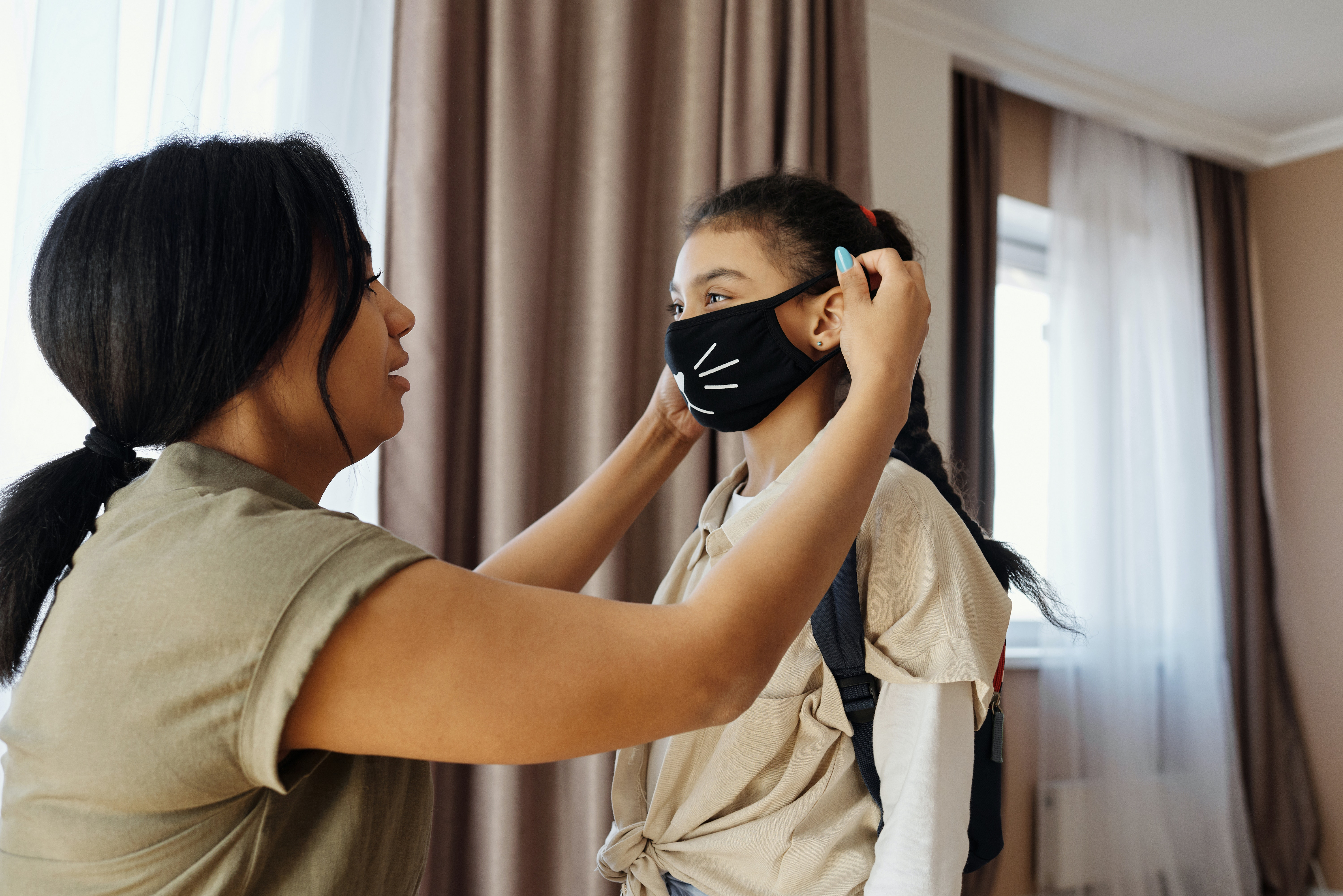Adult helping a child put on a facial mask
