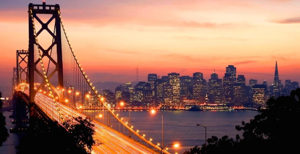 Bay Bridge and city skyline at sunset
