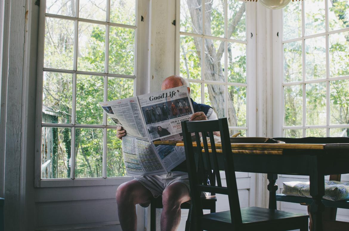 Seated older man reading a newspaper