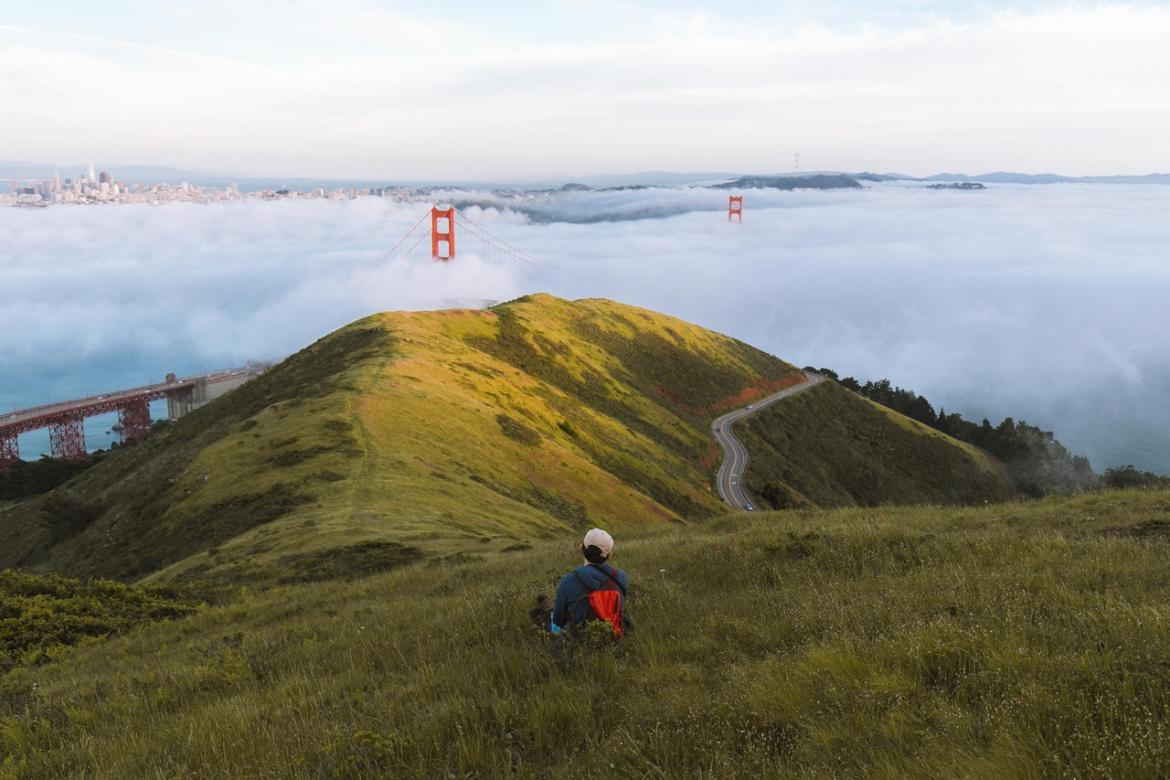 Person sitting the grass looking the Golden Gate Bridge obscured by fog