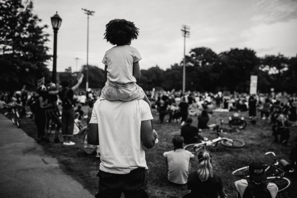 Person with a child on their shoulders looking at a protest or gathering