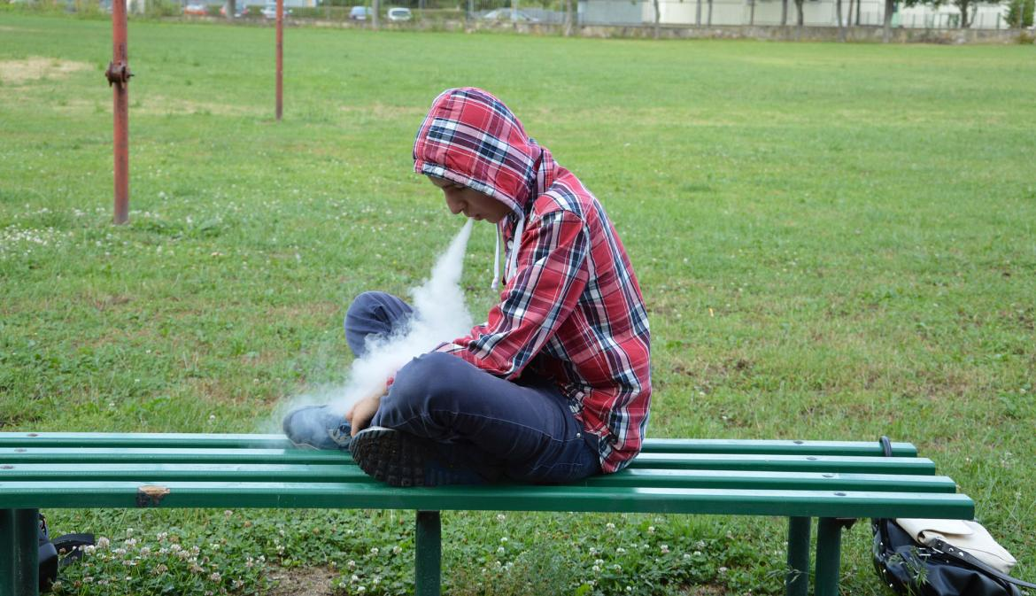 Teen vaping on bench