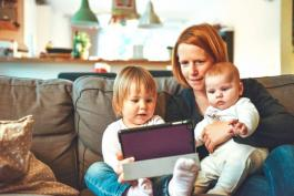 Woman sitting with two small children on a couch while looking at a tablet device
