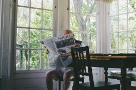 Person sitting a table while reading a newspaper